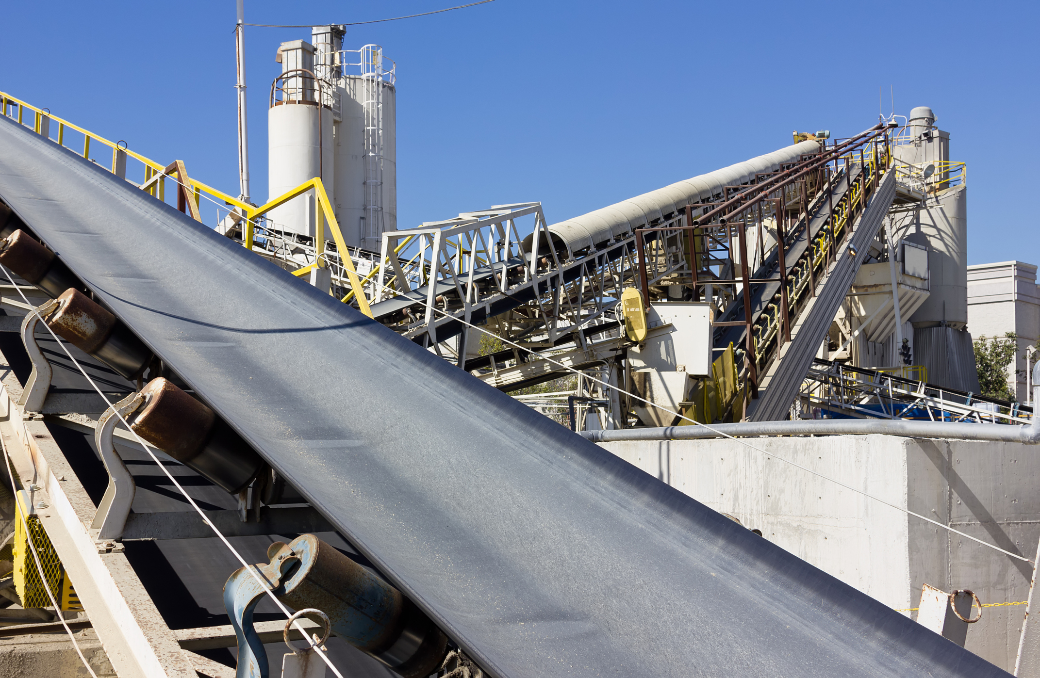 Multiple industrial conveyor belts are used at a processing site.